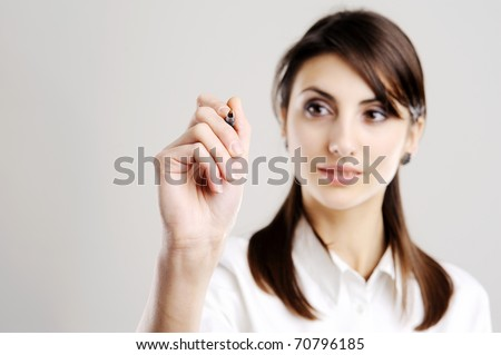 Young business woman drawing on transparent glass