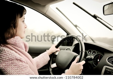 Young business woman driving car in rain (focus on face) - stock photo