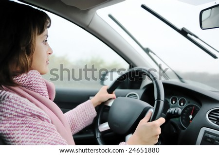 Young business woman driving car in rain (focus on face)