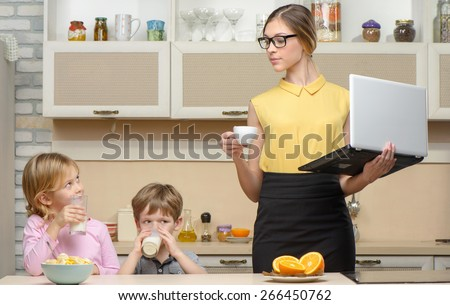 Young business woman early in the morning with her little children. She using laptop. Kitchen interior. Concept for busy mother
