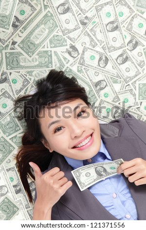 Young business woman happy show thumb up with money and lying on money bed, asian beauty model
