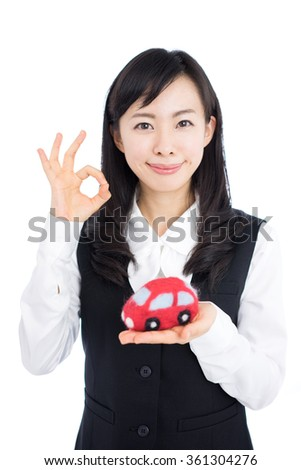 Young business woman holding a car toy, isolated on white background - stock photo