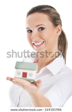 Young business woman holding a house on hand. Isolated on white. - stock photo
