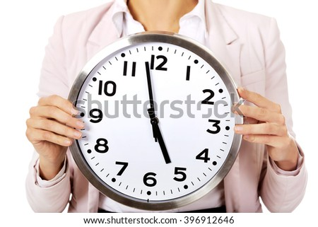 Young business woman holding office clock - stock photo