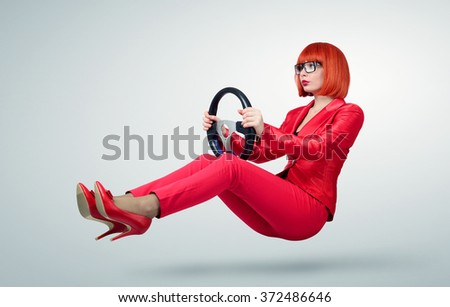 Young business woman in red driver car with a wheel, auto concept.