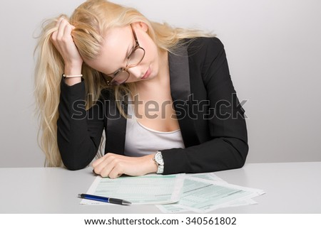 Young business woman in stress with tax forms