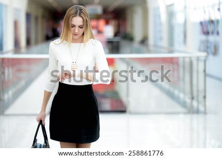 Young business woman in trendy wear hurrying, waiting impatient, looking at her watch in a rush, running errands, copy space - stock photo