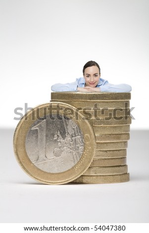 young business woman leaning against a stack of euros - stock photo