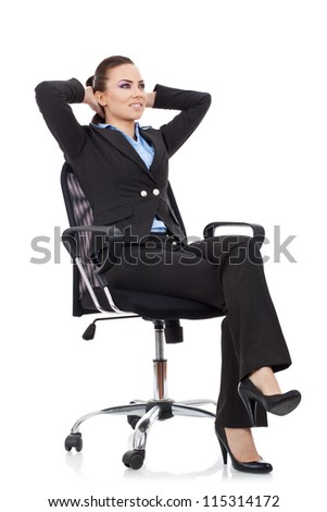 young business woman leaning back in a black chair chilling out, not having any cares - stock photo