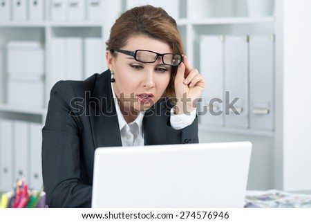 Young business woman looking intently at laptop monitor seeing something unusual - stock photo
