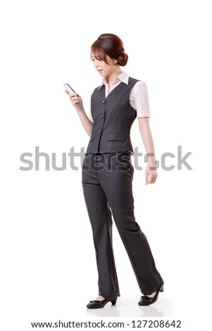 Young business woman looking message on cellphone, full length portrait on white background. - stock photo