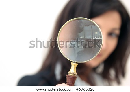 young business woman looks through a magnifier glass - stock photo