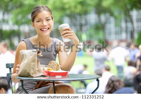 Young business woman on lunch break in City Park drinking coffee and eating sandwich. Happy smiling multiracial young businesswoman in Bryant Park, New York City, USA. - stock photo
