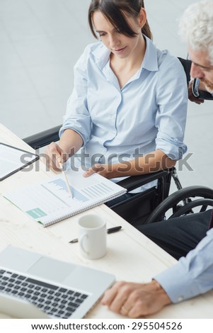 Young business woman on wheelchair working at office desk and checking paperwork with her male colleague, disability and independence concept - stock photo