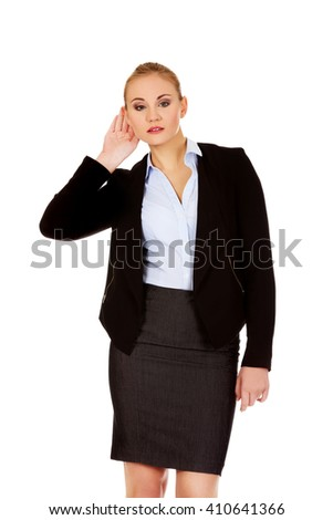Young business woman overhears a conversation - stock photo