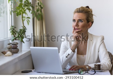 Young business woman pensively sits in front of the laptop in office. - stock photo