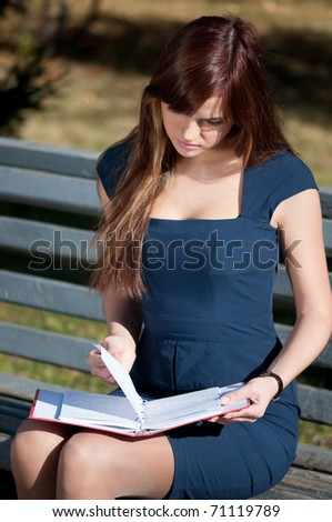 Young business woman planing, writing and reviewing  diary at city park. Student - stock photo