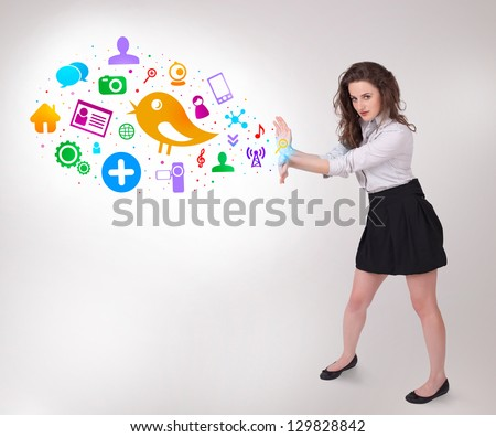 Young business woman presenting colourful social icons on bright background - stock photo