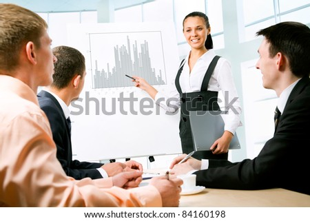 Young business woman presenting his ideas on whiteboard to colleagues