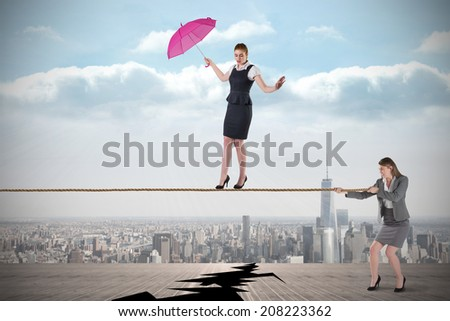 Young business woman pulling a tightrope for businesswoman against cracked balcony overlooking city - stock photo