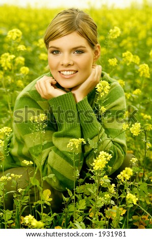 Young business woman relaxing on green meadow full of yellow flowers