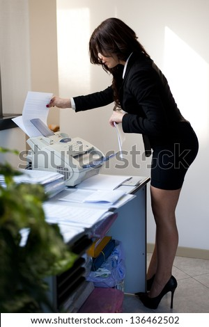 Young Business woman sending fax in office - stock photo