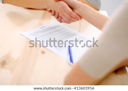 Young business woman shaking hands  after signing contract