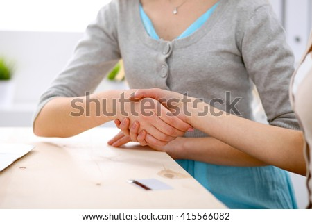 Young business woman shaking hands  sitting at the desk