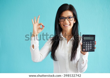 Young business woman show calculator and gesture ok - stock photo