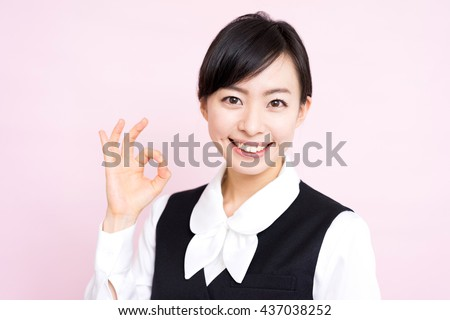 Young business woman showing OK gesture against pink background - stock photo