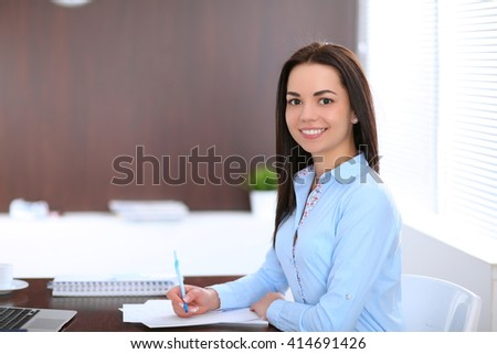 Young business woman sitting and writing at the table  in office - stock photo