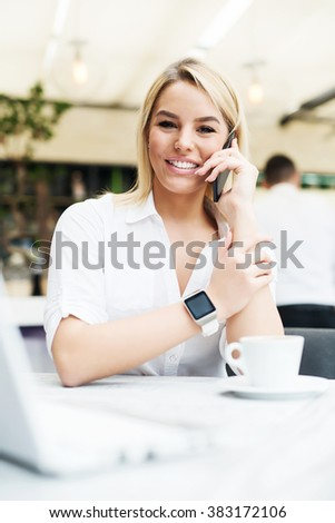Young business woman sitting at cafe bar, talking on smart phone, wearing smart watch. - stock photo