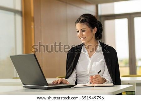 Young business woman sitting at her desk in an office, working on a laptop computer and planning a new project - stock photo