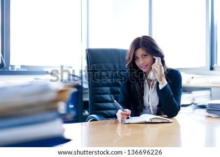 young business woman sitting at the desk talking at the phone on office background - stock photo
