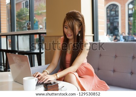 Young business woman sitting in cafe with her laptop. - stock photo