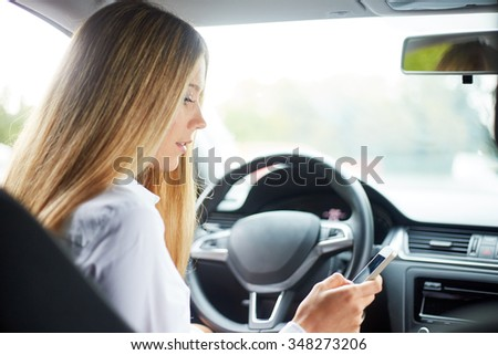 Young business woman sitting in car and writes sms