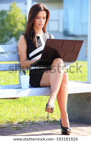 Young business woman sitting on a park bench and using laptop outdoors  - stock photo