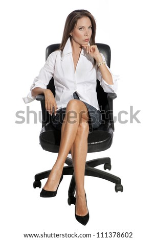 Young business woman sitting on chair against white background - stock photo