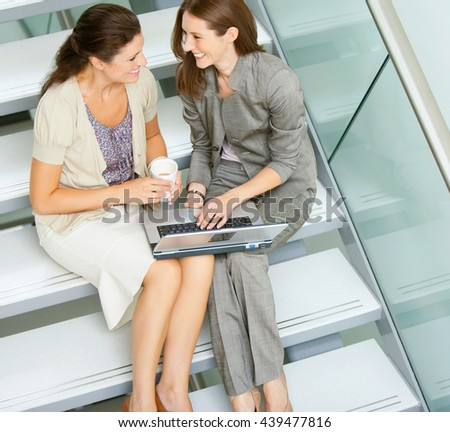 Young business woman sitting on stairs and using laptop - stock photo