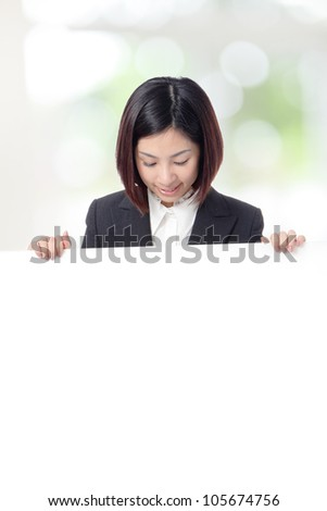 Young Business woman smile look to billboard with empty copy space on green background, model is a asian girl - stock photo