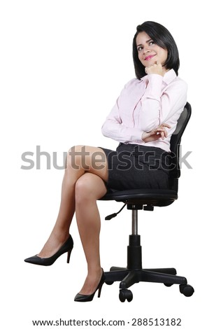 Young business woman smiling and daydreaming at work, sitting on a black chair - stock photo