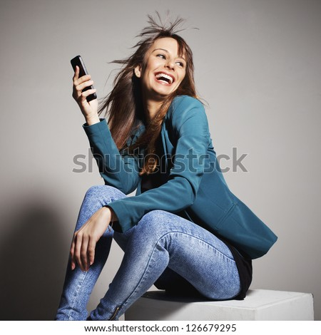 Young business woman smiling with smart phone. Beautiful business woman with mobile phone. On a grey background
