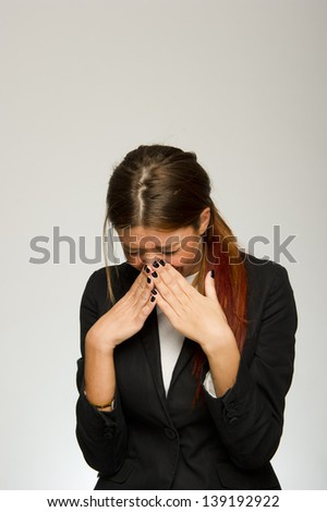 Young business woman sneezing on white background - stock photo