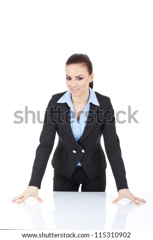 young business woman standing in front of the desk, leaning on it and smiling at the camera. isolated on white - stock photo