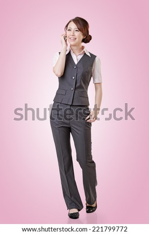 Young business woman talking on cellphone, full length portrait on with clipping path. - stock photo