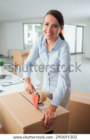 Young business woman taping up a cardboard box in the office, relocation and new business concept - stock photo