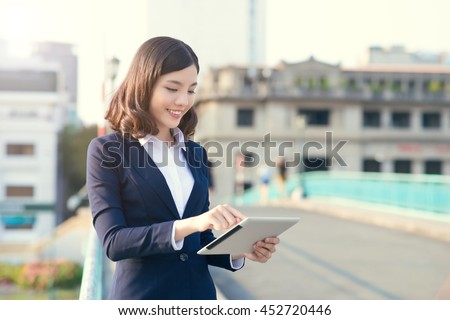 Young business woman using a tablet in the street with office buildings in the background
