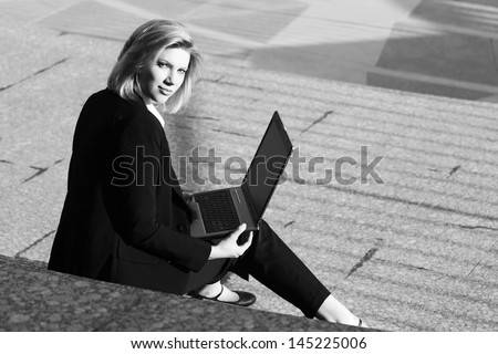 Young business woman using laptop on the steps - stock photo