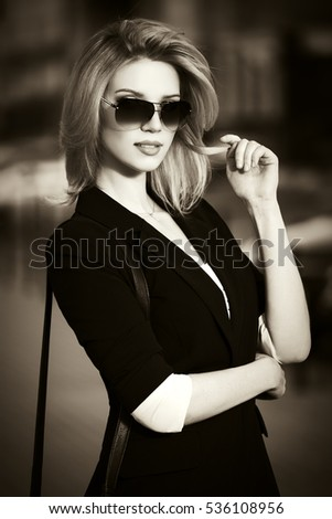 Young business woman walking on city street  Stylish fashion model in sunglasses outdoor
