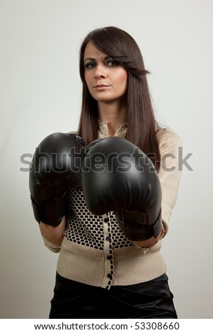 Young business woman wearing boxing gloves. Isolated on white - stock photo